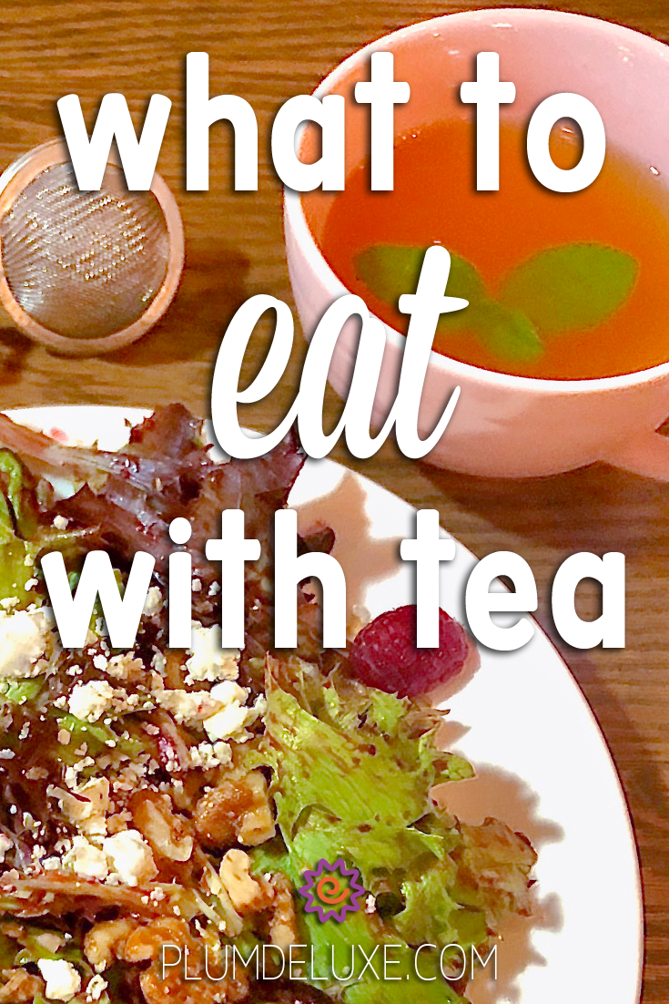 A pink teacup full of tea and a salad sit side by side on a wooden table with a tea ball infuser on the side. The overlay text reads: what to eat with tea.