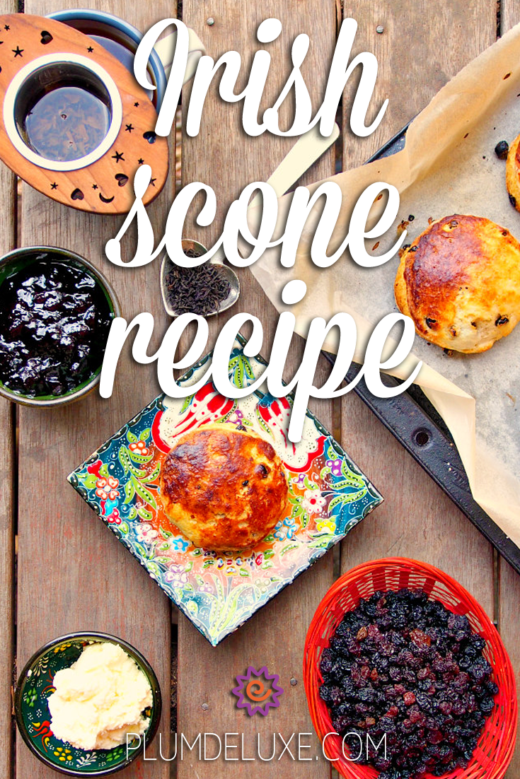 Overhead view of an Irish scone on a floral plate surrounded by black currants, butter, jam, a cup of tea, and a tray of baked scones. The overlay text reads: Irish scone recipe.