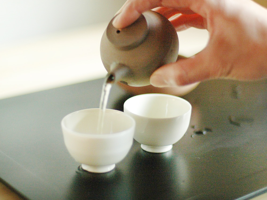 A hand pours tea from a small clay teapot into two small white porcelain cups.