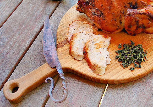 Loose leaf tea and slices of tea smoked chicken rest of a wooden cutting board along with a hand forged iron knife.