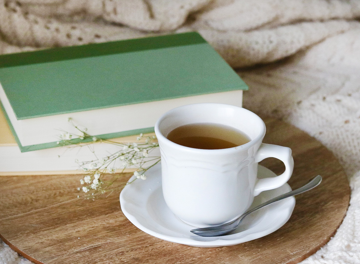 A white teacup full of chamomile tea sits in front of two books and a knit blanket.