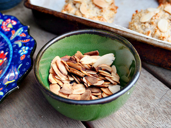 A green bowl full of toasted slivered almonds sits on a wooden table in front of a tray of scones.