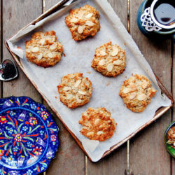 Overhead view of six dairy free scones on a parchment-lined baking tray. They are surrounded by a cup of tea with a Victorian style infuser, a heart-shaped pewter scoop of tea, and a blue and red floral plate.