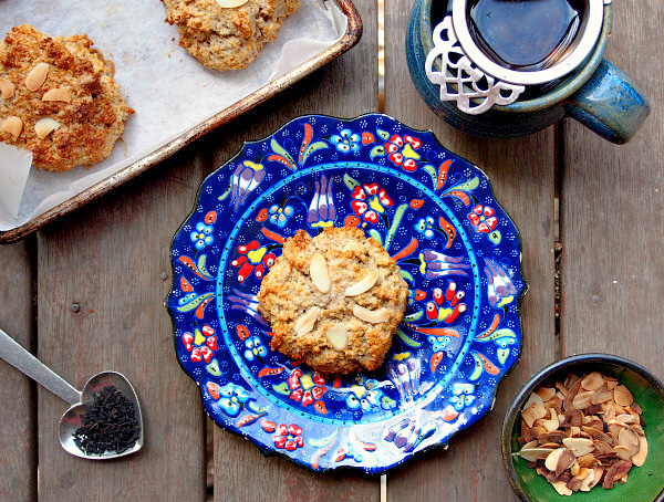 Overhead view of a gluten free dairy free scone with almonds on a blue floral plate. It is surrounded by a heart-shaped scoop of tea, a green bowl of almonds, a cup of tea, and a tray of baked scones.