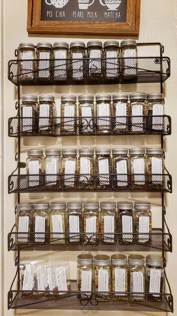 A spice rack is hung on the wall and used to store labeled jars of different loose leaf teas.