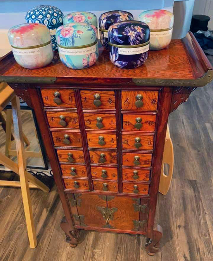 A brown apothecary cabinet is used to store tea. The top holds colorful tins of tea.