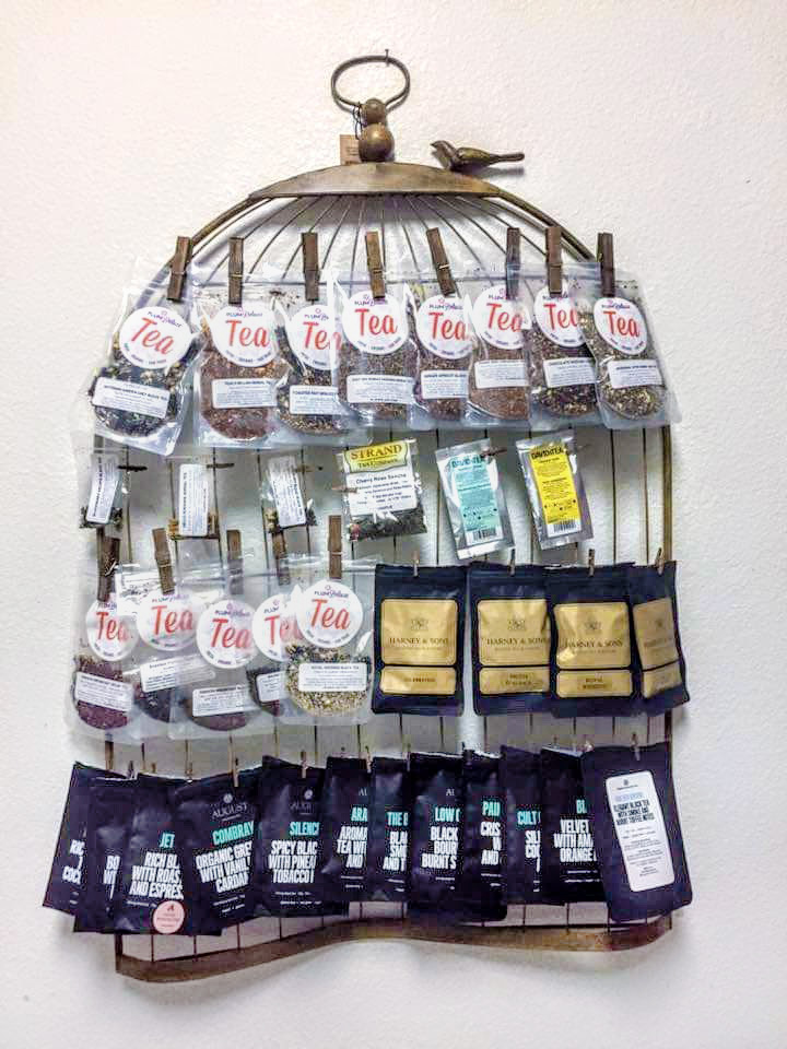 A photo holder shaped like a bird cage is hung on the wall and used to display bags of loose leaf tea instead of photos.