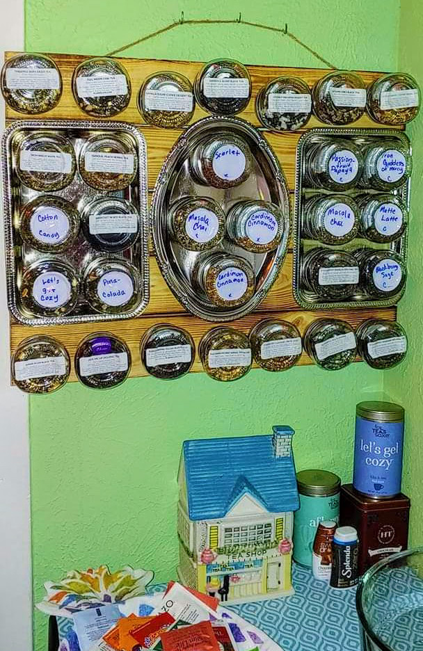A magnetic board is hung on the wall and used to store magnetized metal tins full of tea.