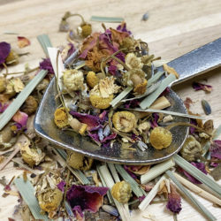 Closeup of a heart-shaped spoon full of chamomile, rose, and lemongrass tea.