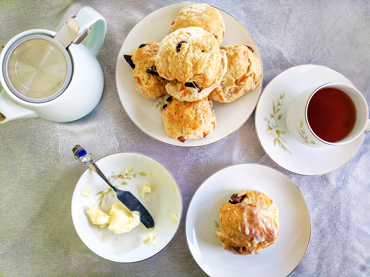 Overhead view of a plate of traditional English tea cakes, a teacup full of tea, a dish of butter, and a teapot.