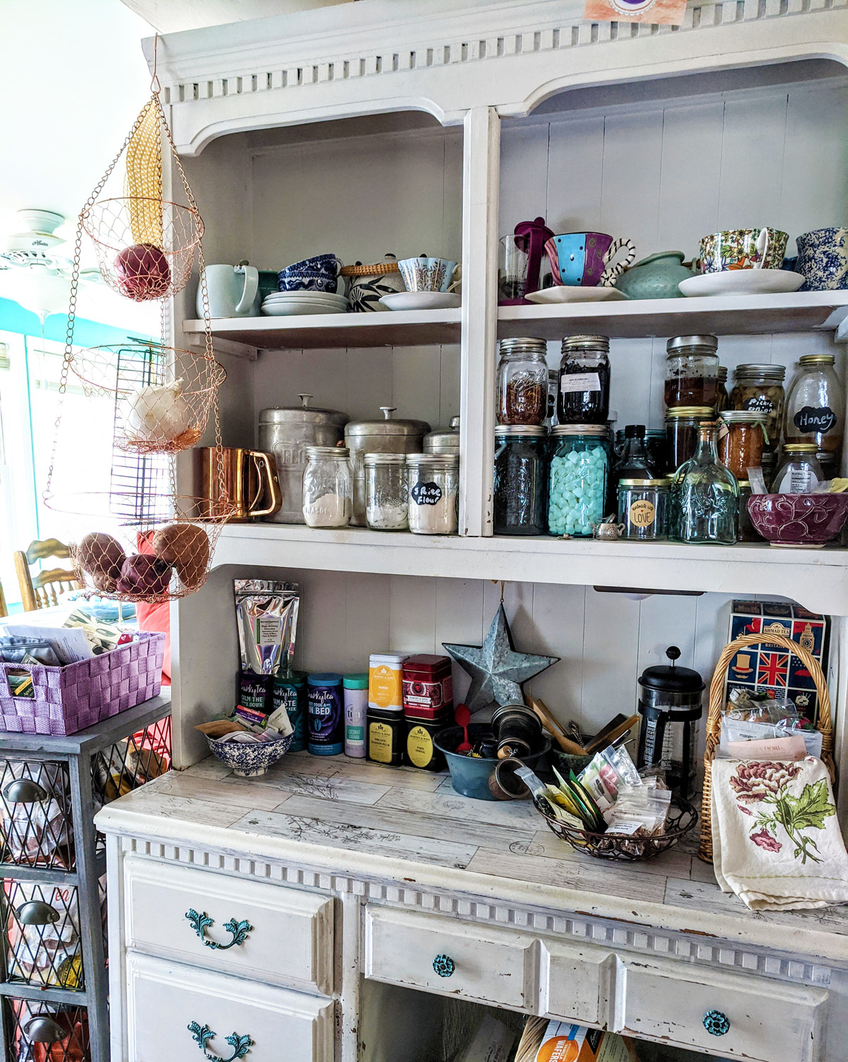A white hutch has been used to store tins of loose leaf tea, mugs, and tea making equipment.