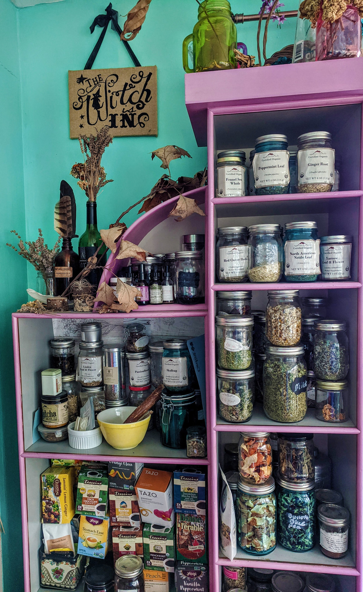 A purple shelf system holds jars of loose leaf tea as well as other pantry items.