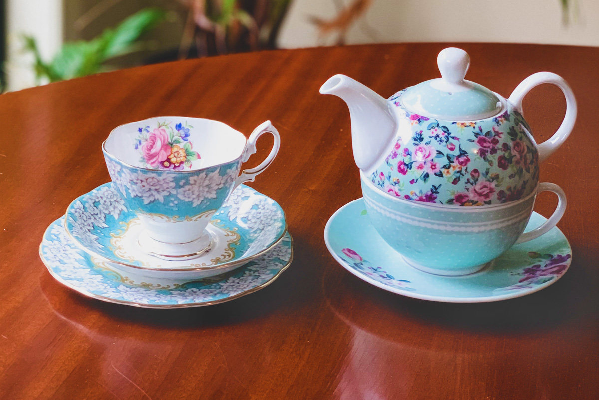A blue and white floral teapot, teacup, and two saucers sits side by side on a polished wooden table.