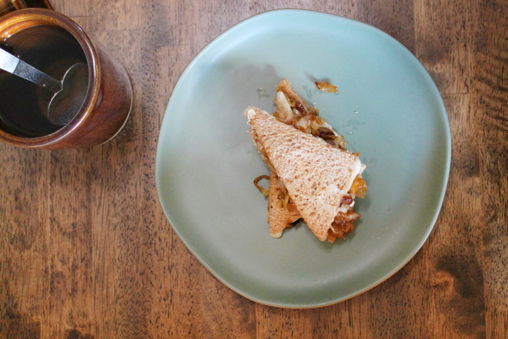 Overhead view of a french onion tea sandwich cut into wedges and served on a light blue plate. Next to it is a brown earthenware mug of tea with a heart-shaped silver spoon in it. They sit on a dark wooden table.