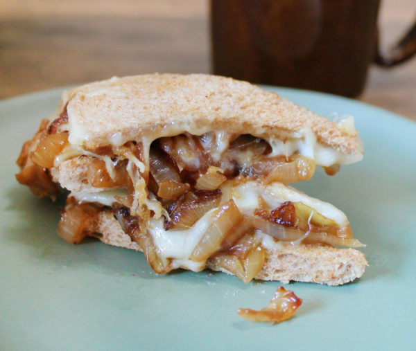 Side view of a french onion tea sandwich with caramelized onions, Gruyere cheese, and sourdough bread, on a light blue plate.