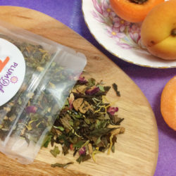 A package of Plum Deluxe loose leaf white tea sits open on a wooden board. Behind it on a purple tablecloth is a plate of fresh apricots.