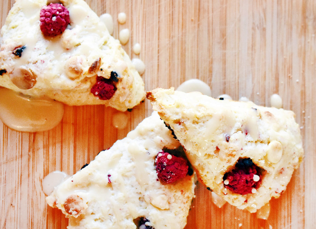 Overhead view of three raspberry white chocolate scones drizzled with glaze on a wooden board.