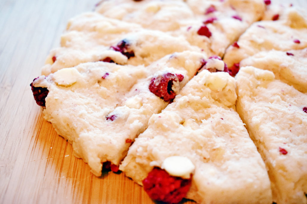 A circle of raspberry white chocolate scones cut into wedges sits on a wooden cutting board.