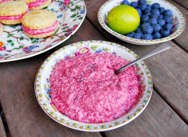 A bowl of blueberry and lime buttercream filling sits on a wooden table.