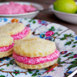 Closeup side view of three Swedish cream cookies with bright pink blueberry lime buttercream on a floral print plate.