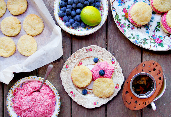 Overhead view of a wooden table with plates and trays of Swedish cream cookies, a bowl of blueberry lime buttercream, a cup of tea with a wooden infuser, and a bowl of blueberries and limes.