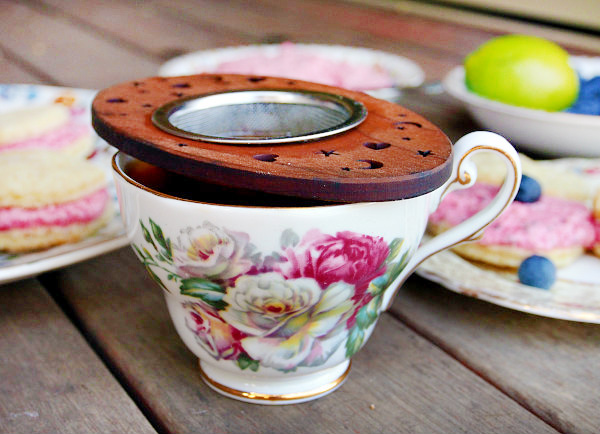 A cherrywood tea infuser sits on top of a white teacup with white and pink flowers.