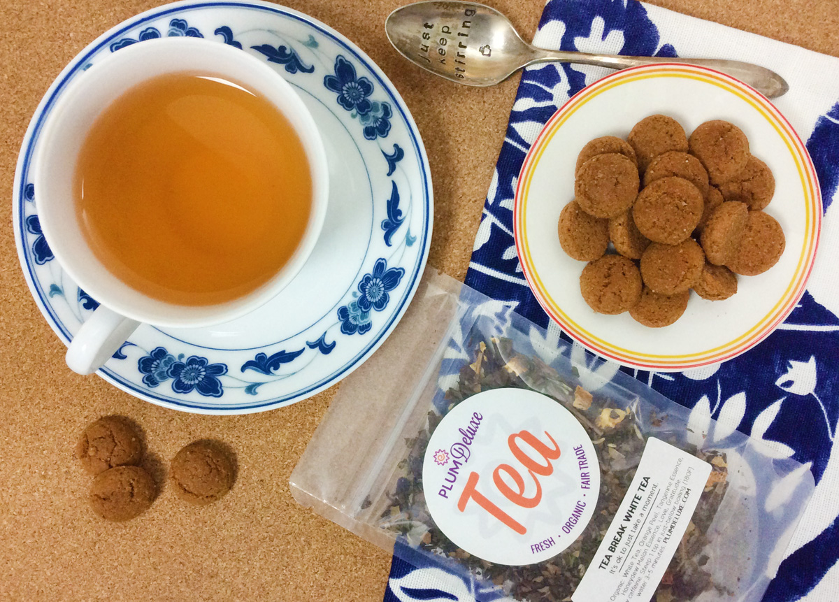 Overhead view of a package of Plum Deluxe loose leaf white tea surrounded by a plate of mini gingerbread cookies and a white and blue floral teacup and saucer full of tea. It all sits on a blue and white tea towel on a cork surface.