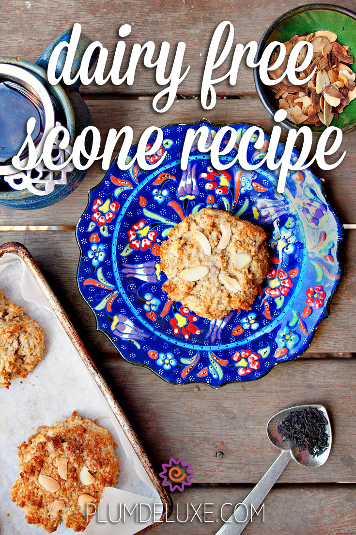 Overhead view of a gluten free dairy free scone with almonds on a blue floral plate. It is surrounded by a heart-shaped scoop of tea, a green bowl of almonds, a cup of tea, and a tray of baked scones. The overlay text reads: dairy free scone recipe.