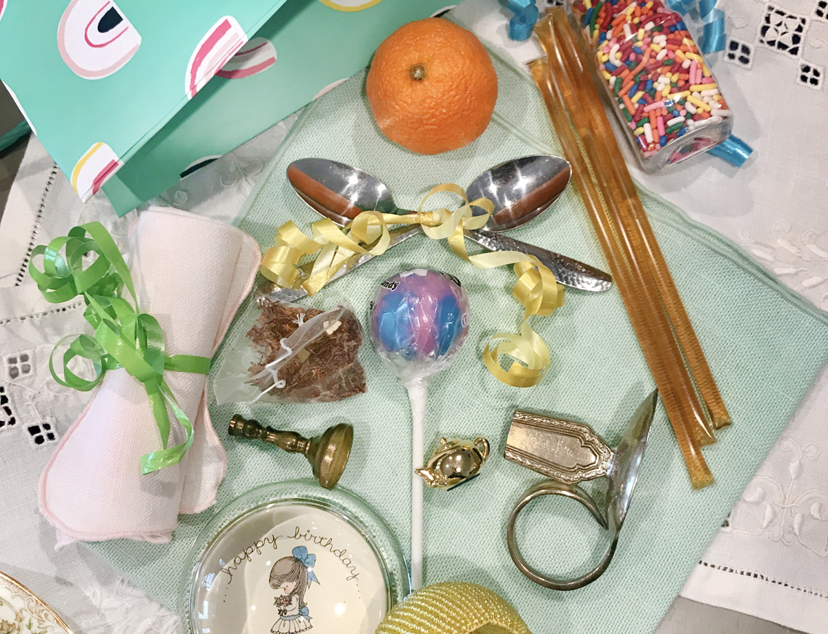 A random assortment of objects – including tea spoons, a lollipop, a paper weight, rainbow sprinkles, and an orange – can be used to play tea party birthday games.