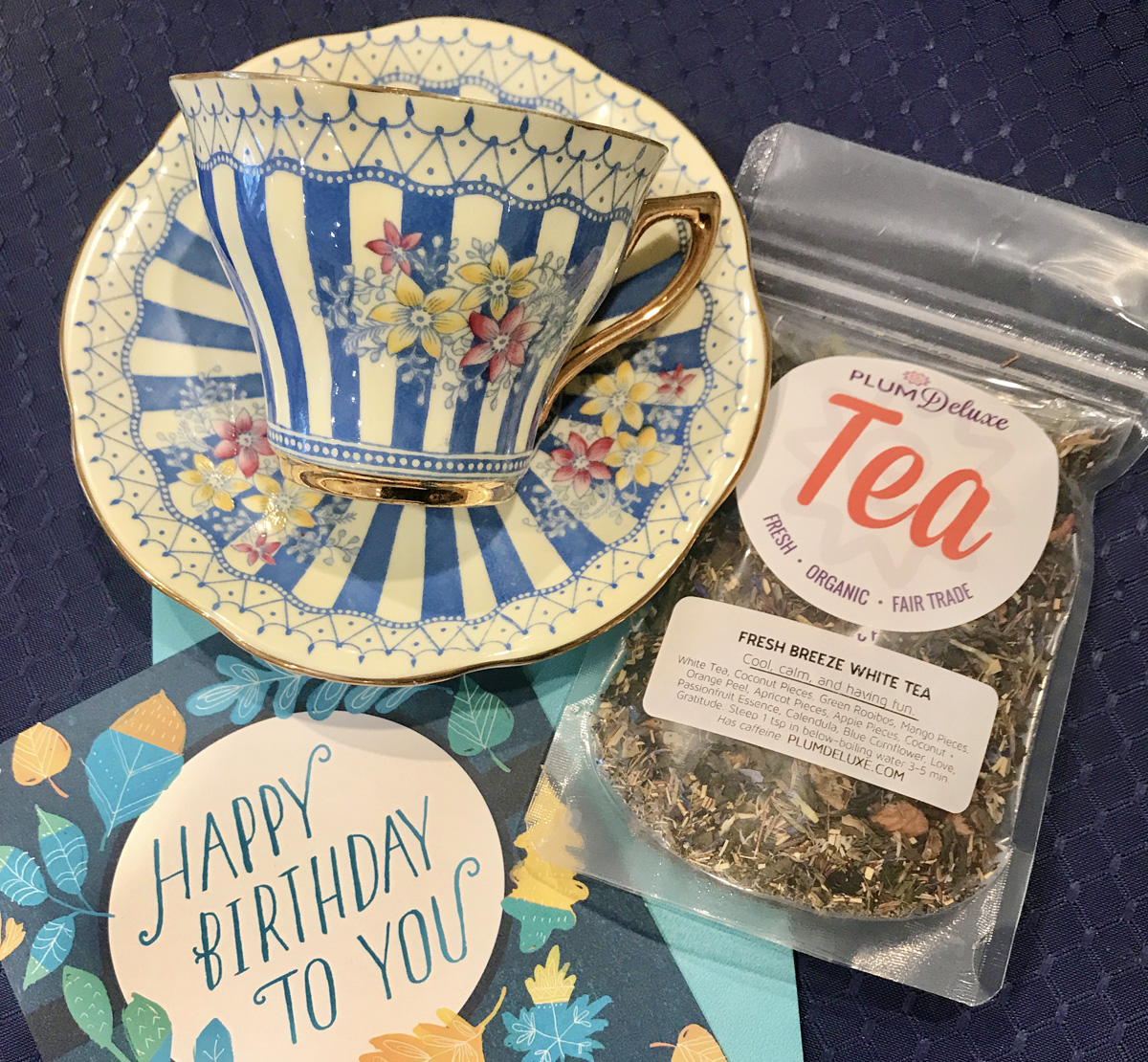"""Overhead view of a blue and white striped floral teacup and saucer, a package of Plum Deluxe loose leaf tea, and a blue and yellow card that says, """"Happy Birthday To You."""""""
