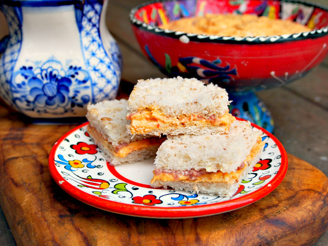 Three pimento cheese tea sandwiches sit on a white and red floral plate. A white and blue mug of tea and a red bowl of pimento cheese spread can be seen in the background.