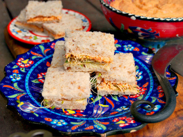 Four vegetarian pimento cheese tea sandwiches sit on a blue floral plate. More sandwiches and a red bowl of pimento cheese spread can be seen in the background.