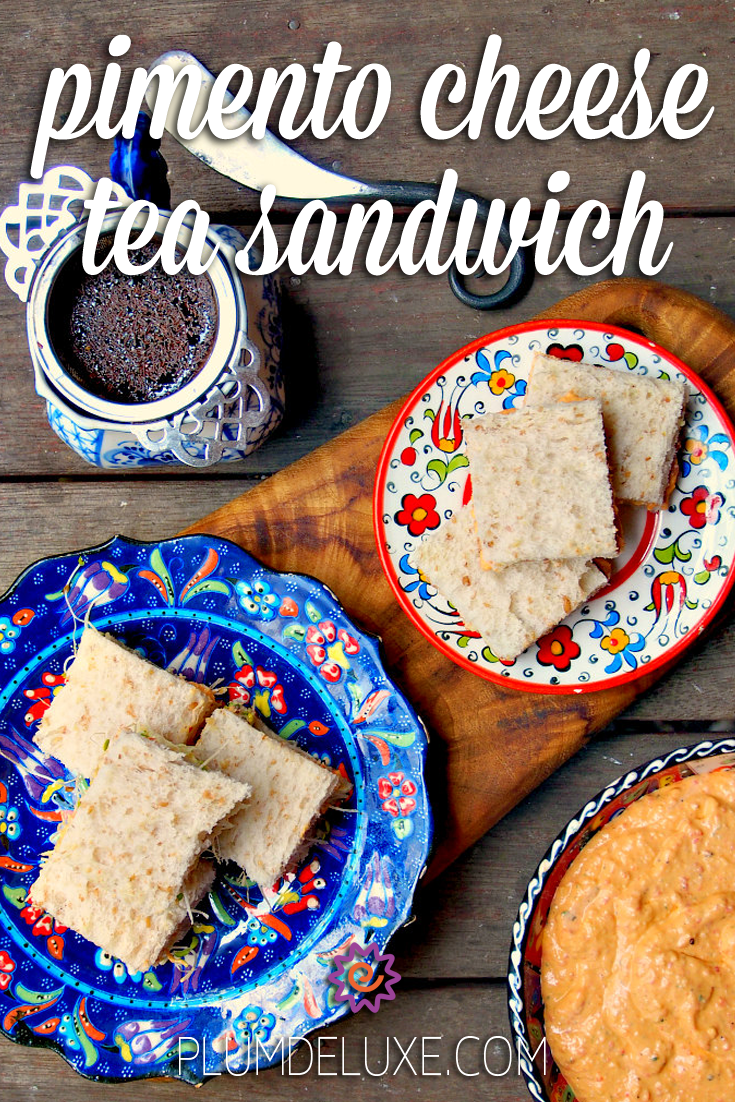 Overhead view of pimento cheese tea sandwiches on blue and red floral plates. They are surrounded by a large bowl of pimento cheese spread, a white and blue mug of tea, and a handmade butter knife. The overlay text reads: pimento cheese tea sandwich.