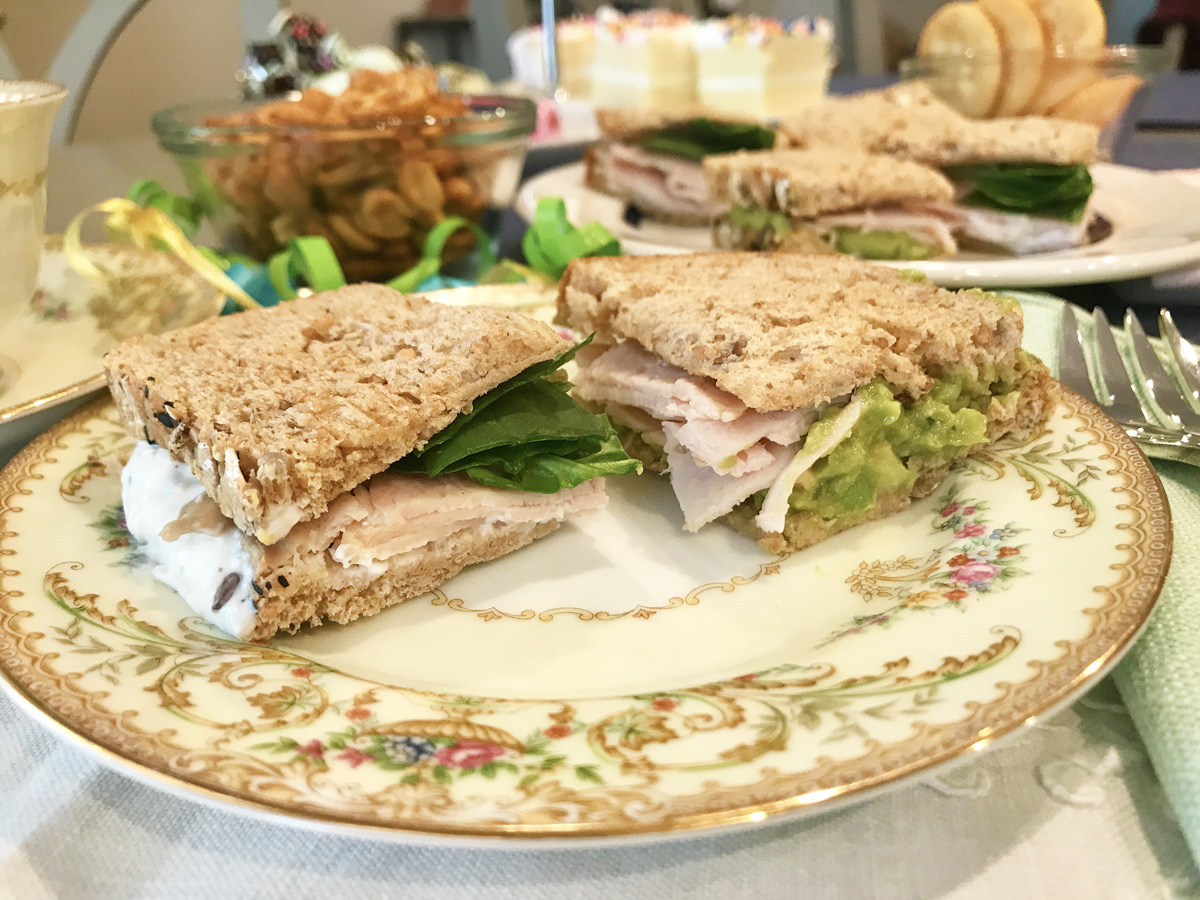 Two tea sandwiches sit on a vintage plate. Other tea party birthday treats can be seen in the background.