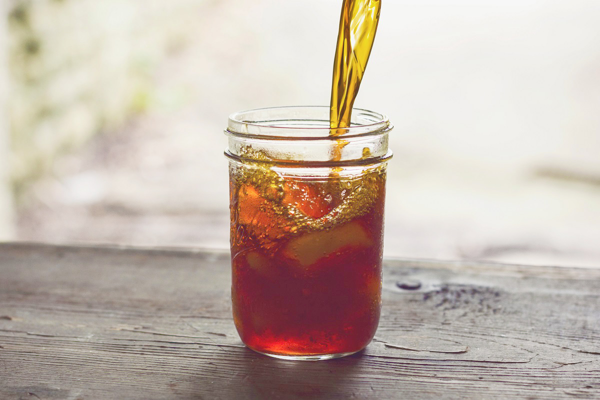 Tea concentrate is poured into a mason jar sitting on a wooden table.