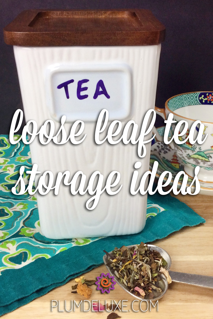 "A white ceramic tea tin with a wooden lid and the word ""TEA"" written on it sits on a green and blue cloth next to a heart-shaped spoon full of loose leaf tea and a blue and white teacup. The overlay text reads: loose leaf tea storage ideas."