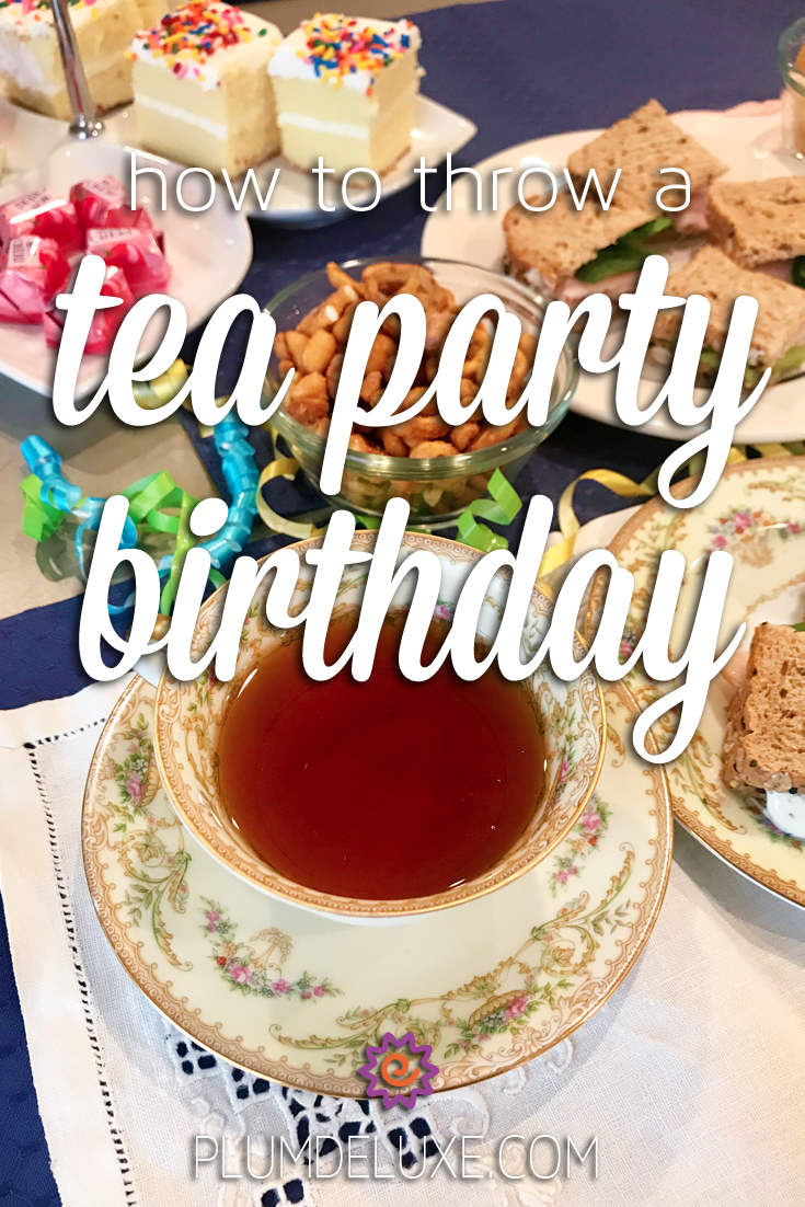 A vintage teacup full of tea, plates of tea sandwiches, bowls of snacks, and a tray of tiny cakes are arranged on white and purple linens. The overlay text reads: how to throw a tea party birthday.