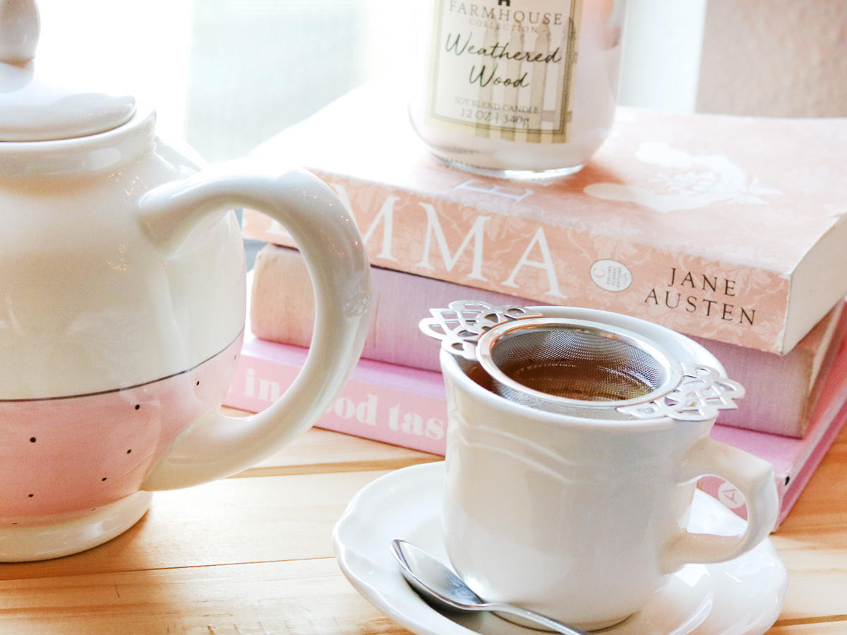 A white teacup and saucer with a victorian style metal infuser sits next to a white and pink teapot in front of a stack of books with a candle on top.