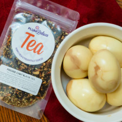 Five tea eggs are displayed in a round white bowl next to a package of Plum Deluxe loose leaf tea. They are sitting on a red running on a wooden table.