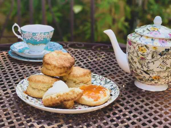 A plate of eggless scones sits on an outdoor patio table next to a white floral teapot and a blue and white floral teacup.