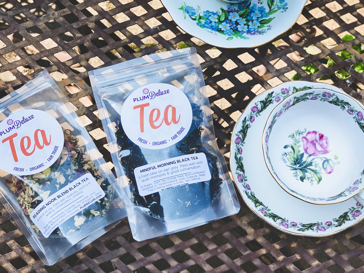 Overhead view of two packages of Plum Deluxe loose leaf tea and a white floral teacup on an outdoor patio table.