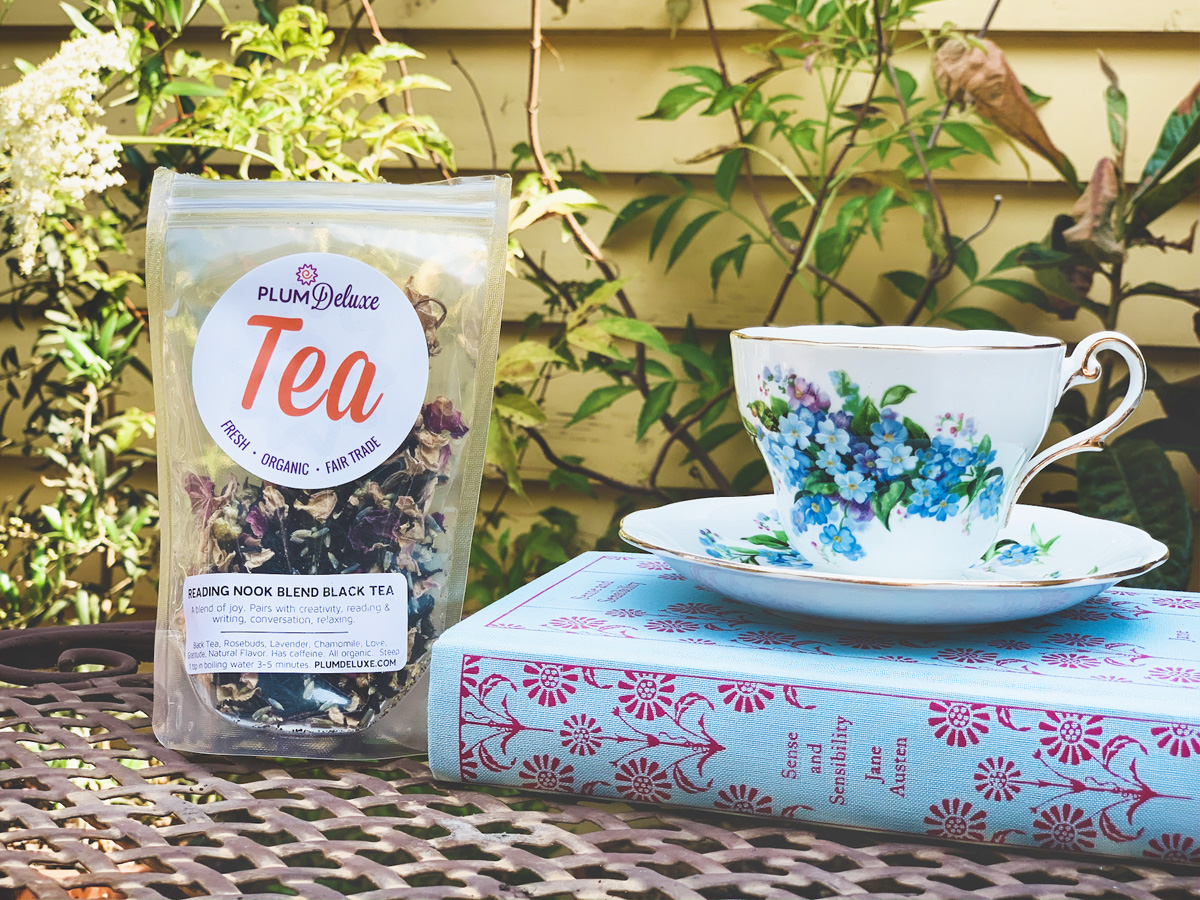 A white floral teacup and saucer sits on top of a book next to a package of Plum Deluxe loose leaf tea on an outdoor patio table.