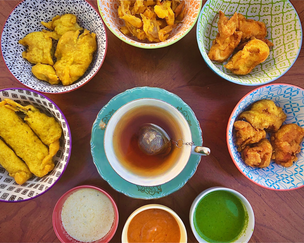Overhead view of a blue teacup and saucer surrounded by brightly colored bowls of chaat, samosa, pakora, and chutney.