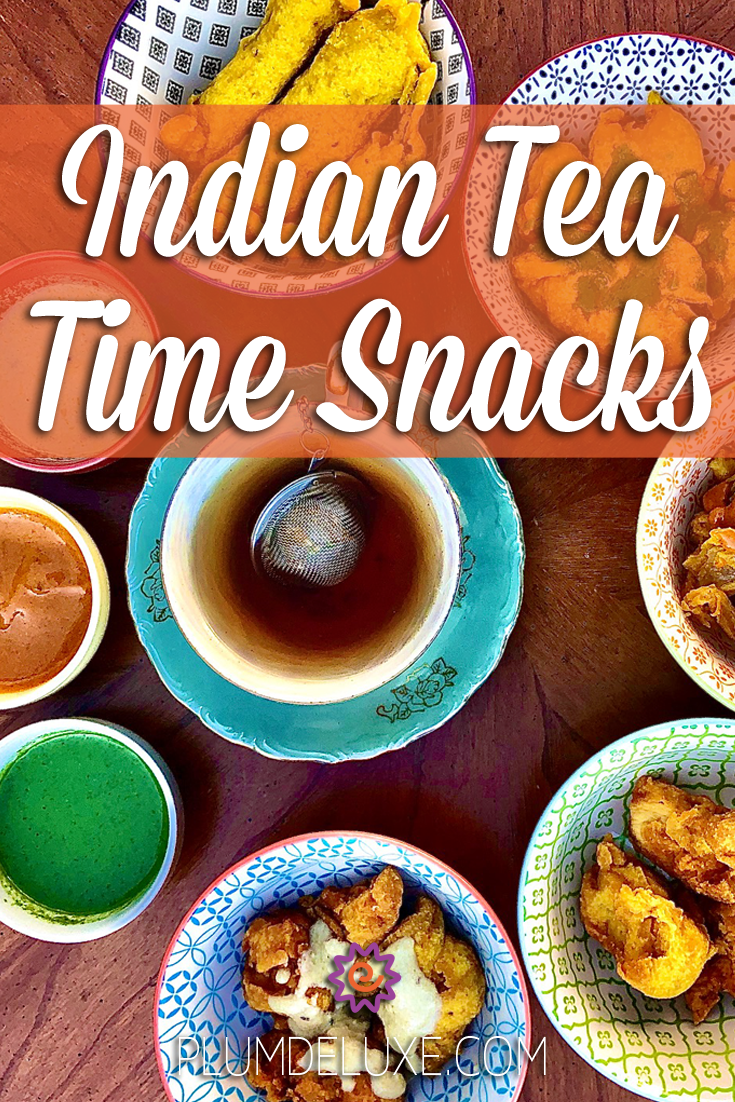 Overhead view of a blue teacup and saucer surrounded by brightly colored bowls of chaat, samosa, pakora, and chutney. The overlay text reads: Indian tea time snacks.