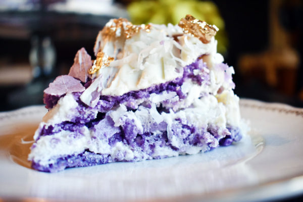 A slice of purple french macaron cake decorated with shredded coconut, buttercream, and edible gold leaf sits on a white plate.