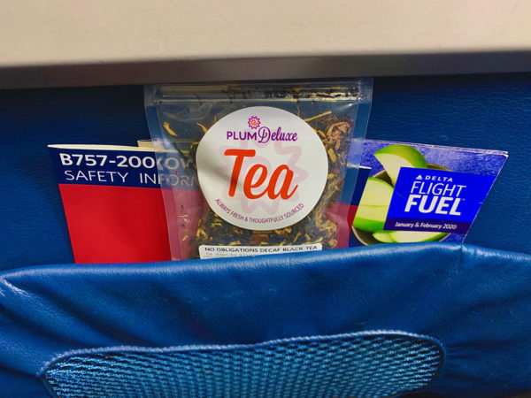 A package of Plum Deluxe tea peeks out of the seat pocket in an airplane. Behind it are several in-flight magazines and safety cards.