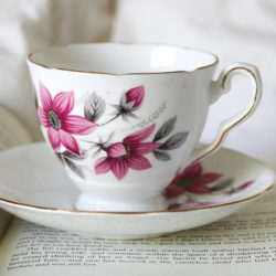 A white teacup with pink flowers sits on top of a book.