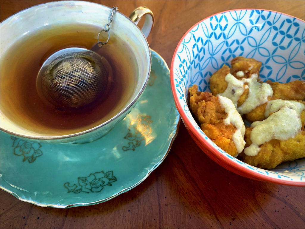 A turquoise and gold teacup and saucer sits next to a blue and white bowl holding pakora and chutney.