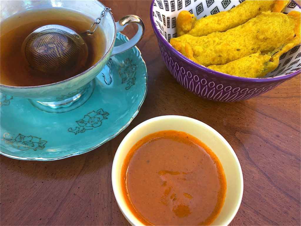A turquoise and gold teacup and saucer sits next to a blue and white bowl of pakora and a small white bowl of red chutney.
