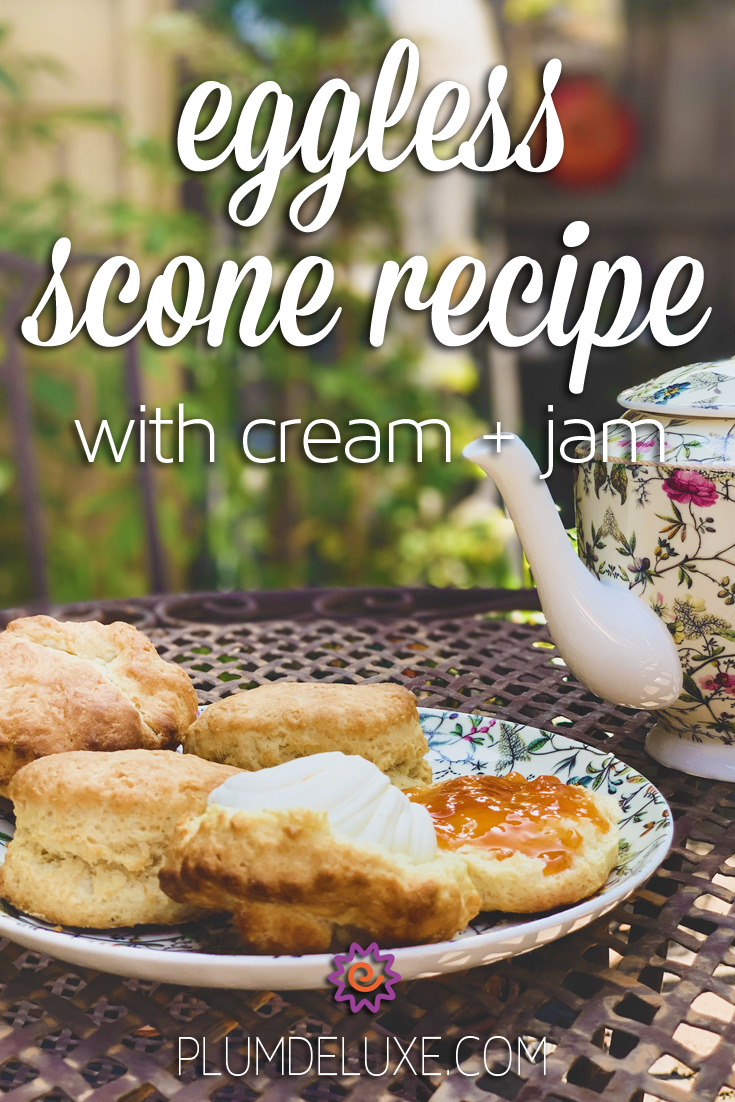 A plate of eggless scones sits on an outdoor patio table next to a white floral teapot. The overlay text reads: eggless scone recipe with cream and jam.